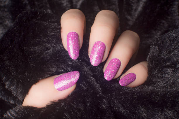 glittered pink nails manicure Female hand with glittered pink nails is holding black fur, manicure and nail care concept. pink nail polish stock pictures, royalty-free photos & images