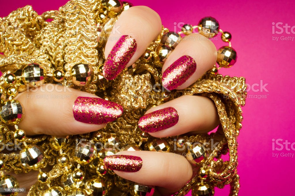 Female hand with gold glittered pink nails is holding gold pearl...
