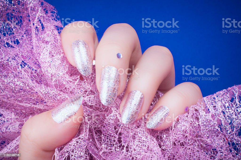 Female hand with glittered purple pink nails is holding glittered...