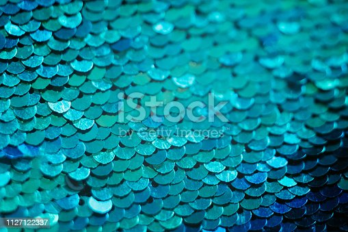 Glittering textile design. Blue sequin background. Mermaid scale concept.