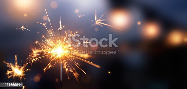 Glittering burning sparkler against blurred bokeh light background