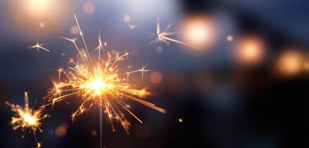 brillante destello ardiente contra fondo de luz bokeh borrosa - año nuevo fotografías e imágenes de stock