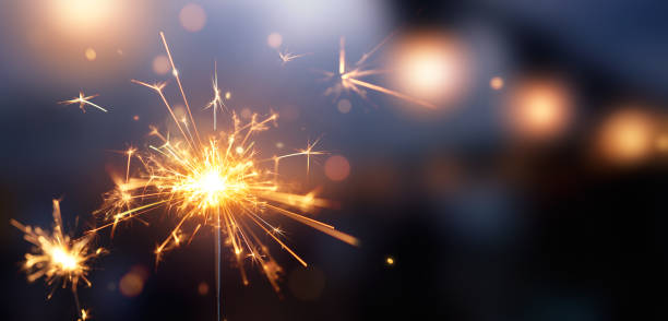 glittering burning sparkler against blurred bokeh light background - fireworks stock pictures, royalty-free photos & images