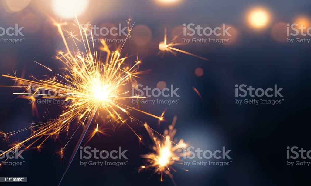 Glittering burning sparkler against blurred bokeh light background Glittering burning sparkler against blurred bokeh light background 2020 Stock Photo