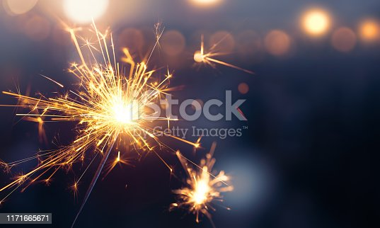 istock Glittering burning sparkler against blurred bokeh light background 1171665671