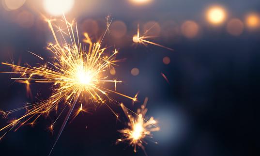 Glittering Burning Sparkler Against Blurred Bokeh Light Background Stock Photo - Download Image Now
