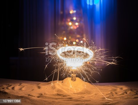 505891566 istock photo Glittering burning sparkler on snow with blurred Christmas tree on dark background. New Year Holiday concept with empty space for your text 1078911394