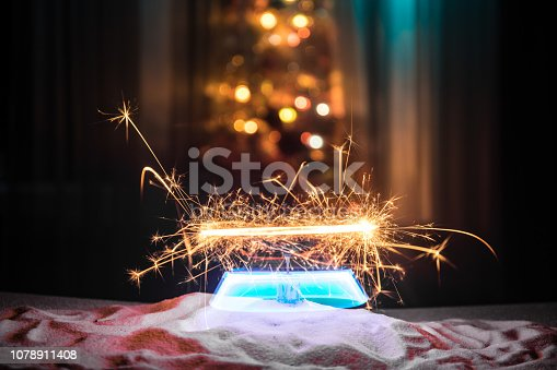 505891566 istock photo Glittering burning sparkler on snow with blurred Christmas tree on dark background. New Year Holiday concept with empty space for your text 1078911408