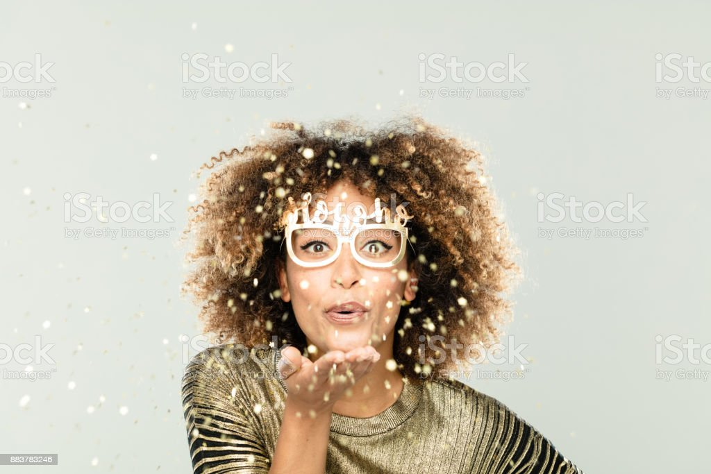 Glittering christmas portrait of beautiful young woman in gold sparkles stock photo