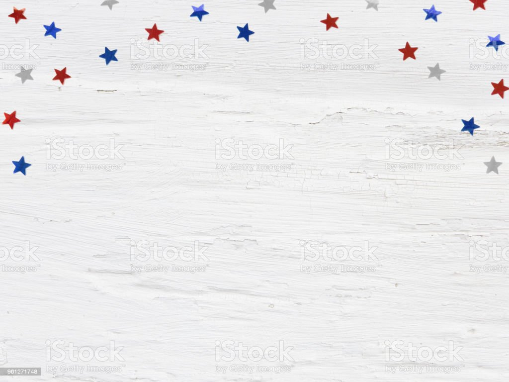 Glittering confetti stars on old grunge wooden background. 4th July, Independence day, card, invitation in usa flag colors. Top view, flat lay, empty space. stock photo