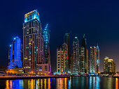 The high rise hotels and luxury apartment blocks, construction cranes and shopping malls of the Dubai Marina illuminated against the blue dusk sky reflecting in the tranquil waters below. ProPhoto RGB profile for maximum color fidelity and gamut.