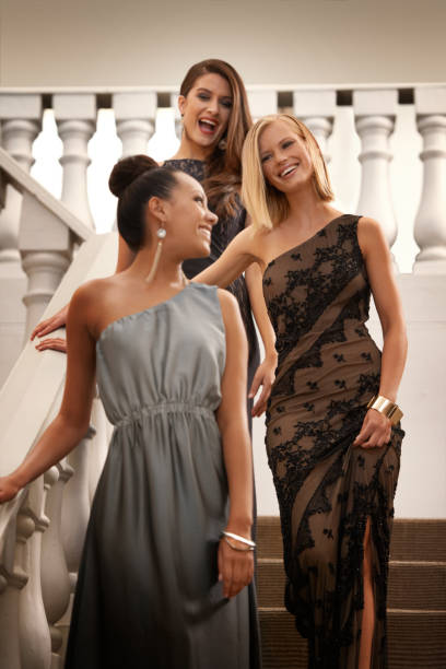 Glitz and glamour Shot of beautiful women standing on an ornate staircase evening wear stock pictures, royalty-free photos & images