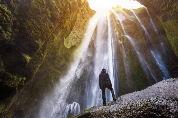 Gljufrabui waterfall in South Iceland,  adventurous traveller standing in front of the stream cascading into the gorge or canyon, hidden Icelandic landmark, inspirational landscape stock photo