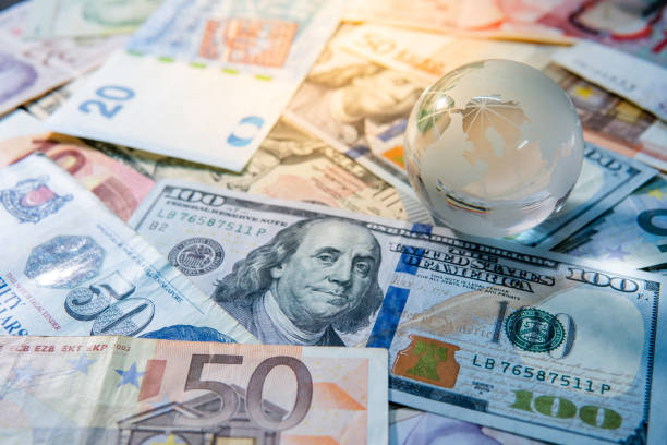 global business and economy. world globe crystal glass on various international money banknotes. currency exchange rate. financial investment concept - exchange rate stock pictures, royalty-free photos & images