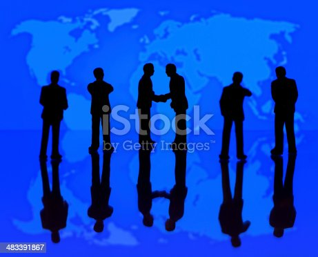 Businessman figurines standing in front of world map.