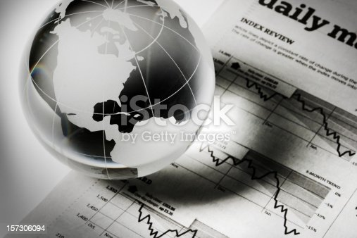 A glass globe paperweight resting on newspaper financial page charts and graphs, which indicate downward global business, investment, and finance trends. The earth sphere casts a shadow, implying recession and forecasting stock market trouble. The USA, Canada, parts of Europe and the Americas are visible, for concepts of world economy.