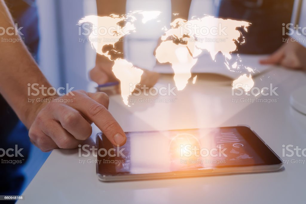 Global business concept, world map hologram, business team Global business concept with a world map hologram above a digital tablet and a team of two businessmen in background Abstract Stock Photo