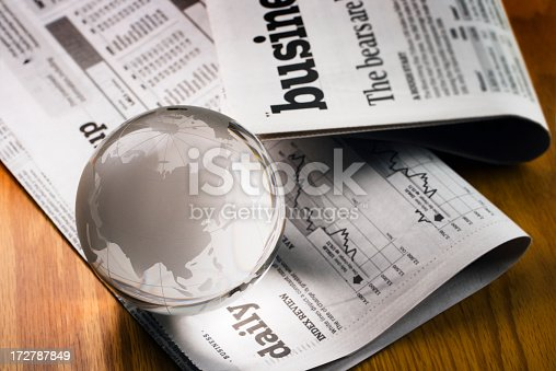 A glass globe paperweight resting on newspaper financial pages, representing international business markets and global finance. The earth sphere implies fortune telling economic trends and forecasting stock market activity for investment success in a recession or unstable market. China, India, and Japan are visible, for concepts of Asian world economy.