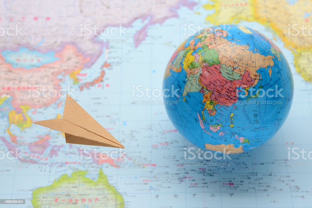 Global business image, paper airplane flying over world map stock photo