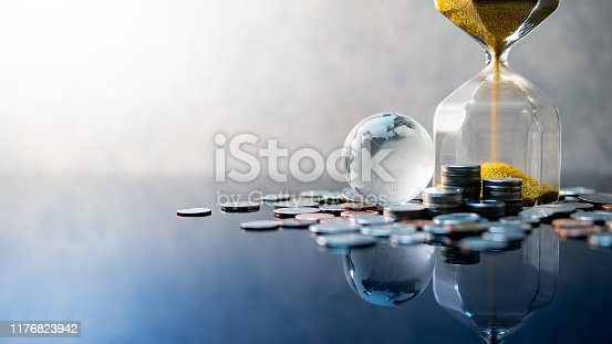 Global business investment growth. Wealth concept. Gold sand running through the shape of modern hourglass with world globe crystal glass and US dollar coins on blue reflective table.