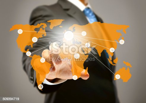 Businessman using touch screen and touching world map.