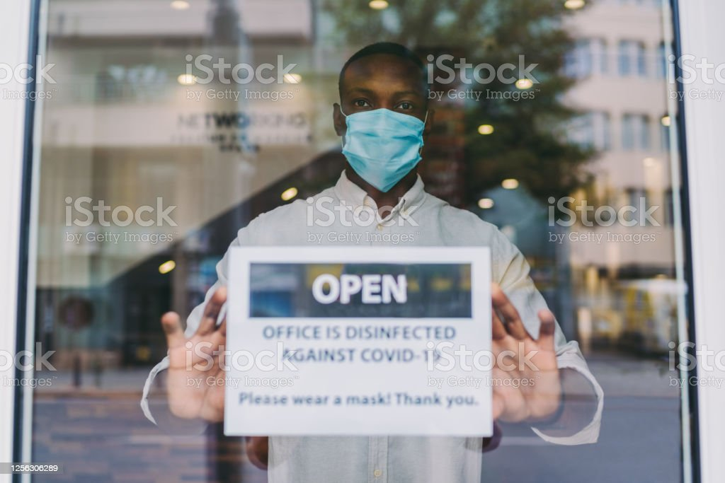 Global business reopening again after COVID-19 pandemic Businessman putting open sign on front office door with notice saying the building is disinfected against COVID-19 Adult Stock Photo