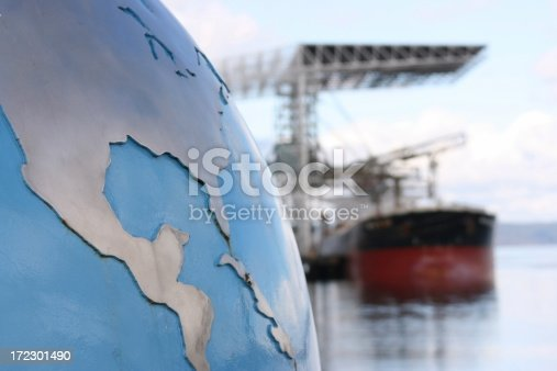 A globe with focus on the United States (USA) and Central America contrsted against a blurred background of a bulk cargo ship exemplifying the global nature of the cargo industry. Look at more