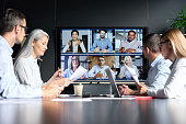 istock Global corporation online videoconference in meeting room with diverse people sitting in modern office and multicultural multiethnic colleagues on big screen monitor. Business technologies concept. 1325899588