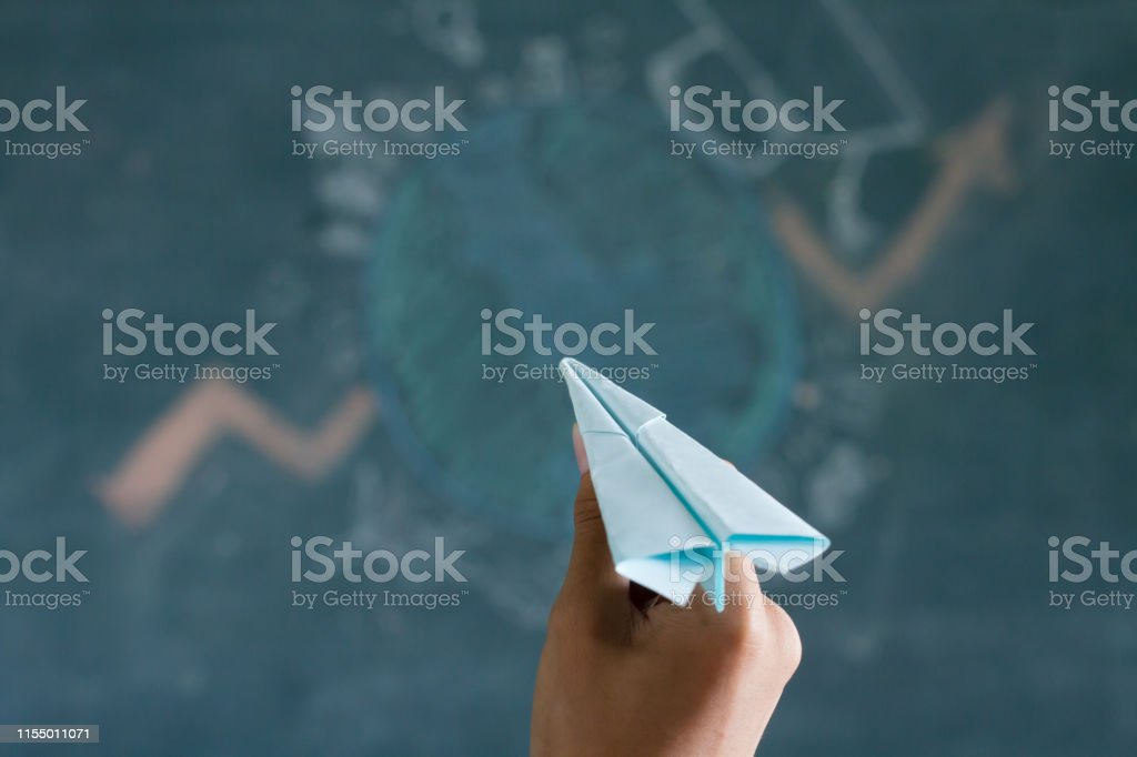 Hand hold a paper plane and try to throw to the education global...