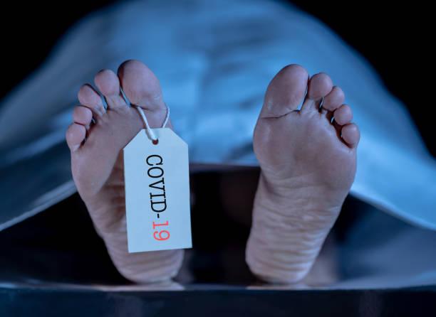 Globale Gesundheitskrise. Bild von Füßen mit COVID-19 auf Zehenmarke eines toten Körpers Opfer der Coronavirus Infektionskrankheit geschrieben. Heidealarm, da die Zahl der Virustoten in Ländern auf der ganzen Welt steigt. – Foto