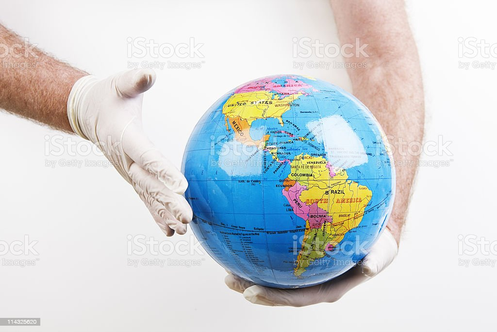 Global health | Doctor wearing gloves holds globe royalty-free stock photo