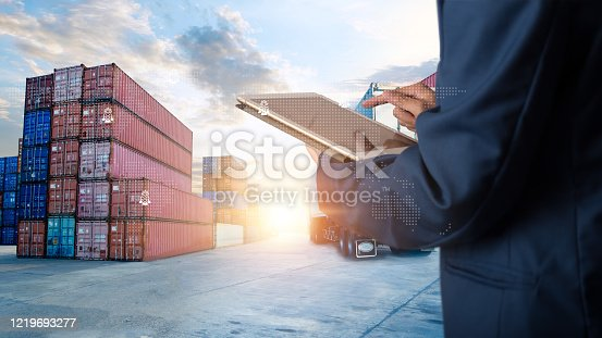 istock Global logistic or world of logistic concept. Businessman or manager using tablet standing with world map icon and shipping yard container and truck of transport background. fast or instant shipping. 1219693277