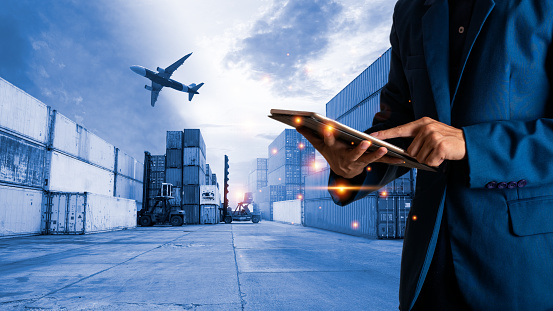 Global logistic or world of logistic concept. Businessman or manager using tablet standing with world map icon and shipping yard container and truck of transport background. fast or instant shipping.