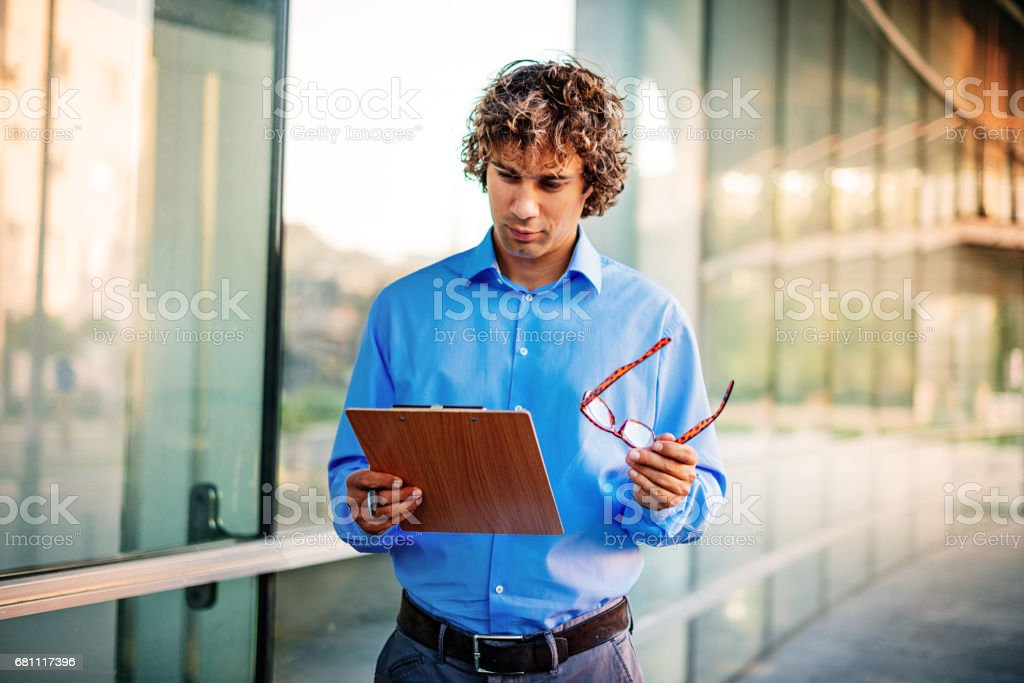 Portrait of young modern businessman, in businesswear, using his...