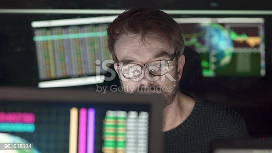 A bearded man studying computer displays depicting global trends with figures, the screens being reflected in his glasses as well as behind him on a black glass wall. The subject matter on the screens pertains to ecology, economics and global trends.