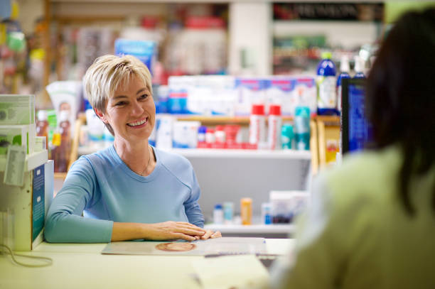 Global Pharmacies A beautiful blond Caucasian female customer smiling friendly at the pharmacist standing at the pharmacy counter Stellenbosch South Africa generic drug stock pictures, royalty-free photos & images