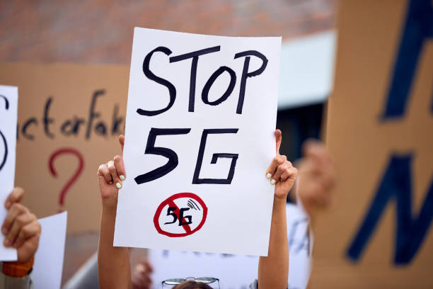 Global protest against 5G network! Close-up of activist holding Stop 5G sign while protesting on city streets. anonymous activist network stock pictures, royalty-free photos & images