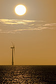 Global warming and climate change. Wind and solar power. Solitary offshore wind turbine at sunrise or sunset. Tranquil spiritual image taken off the East coast of England, UK