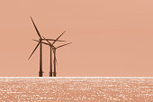 Global warming. Offshore wind farm turbines with twilight orange sky. Simple sparse and foreboding image representing the future of climate change. Natural eerie warm color with copy space.