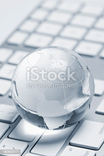 Detail shot of a crystal globe sitting on a computer keyboard.