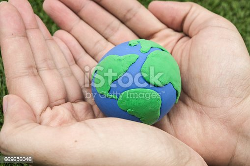 Globe ,earth made from clay in hand on green background. Concept Save green planet. Earth day holiday concept