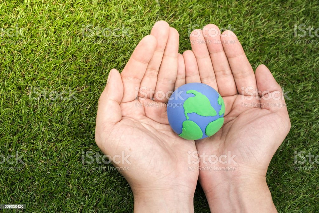 Globe ,earth made from clay in hand on green background. Concept Save green planet. Earth day holiday concept stock photo