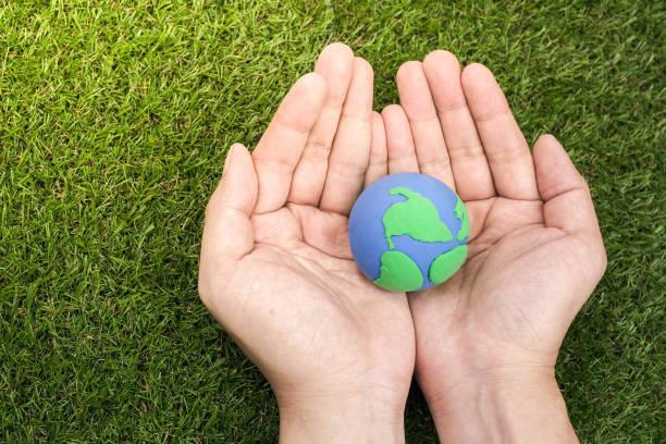 globus, erde, hergestellt aus ton in der hand auf grünem hintergrund. konzept sparen grünen planeten. earth day ferienkonzept - tag der erde stock-fotos und bilder