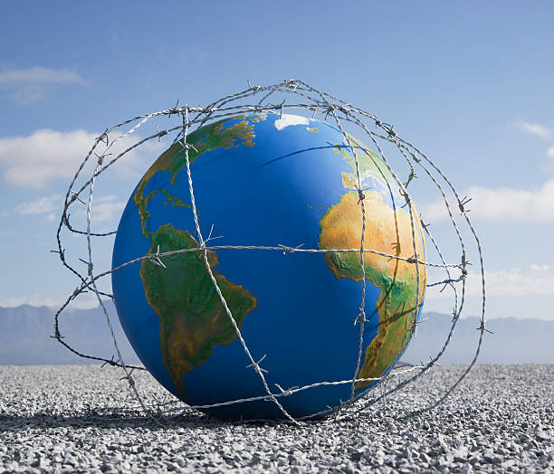 A globe entangled in barbed wire stock photo
