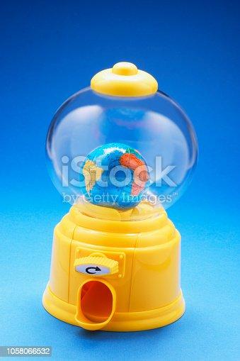 Globe in Bubblegum Machine on Blue Background