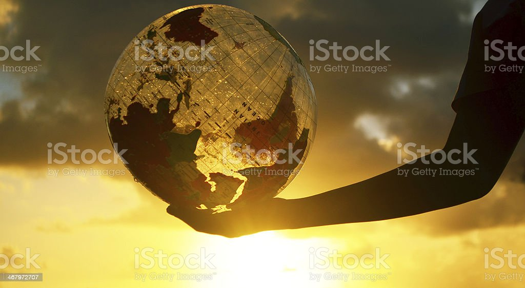 globe in hand and spectacular sunset stock photo