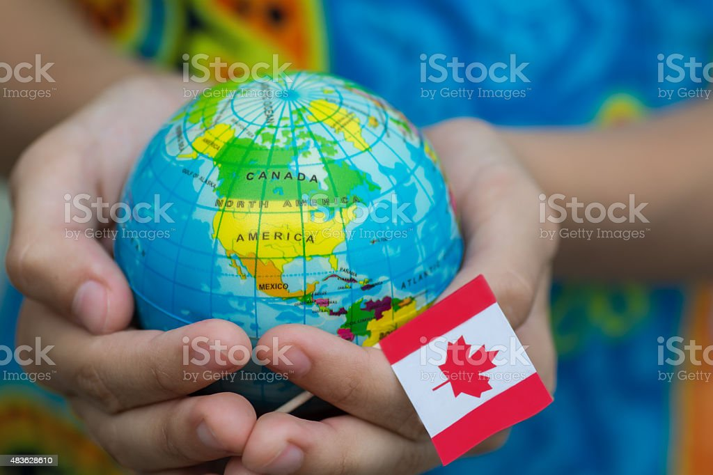 Globe in hand with the Canada flag stock photo