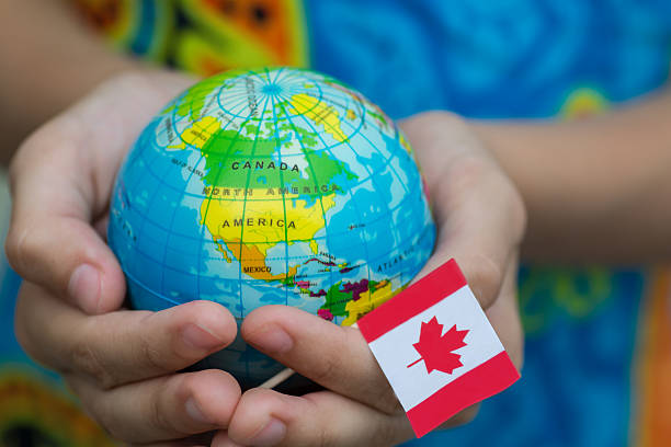 globe in hand with the canada flag - canada travel stock photos and pictures