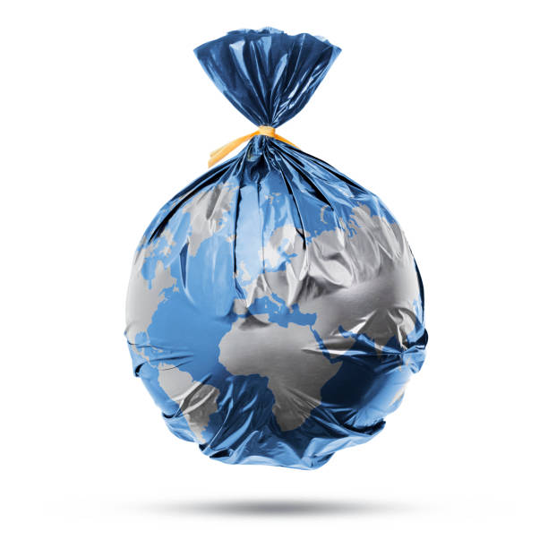 Globe of the earth in a plastic black bag like trash on white background stock photo