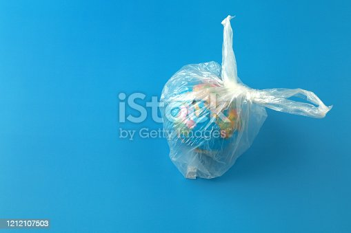 Top view a globe of the earth in a plastic transparent bag like trash on blue background.